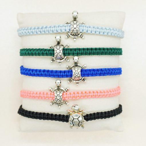Makramee-Armband mit silberner Schildkröte in verschiedenen Farben.