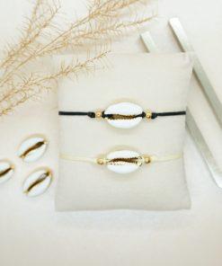 Zartes Armband mit Kauri-Muschel in verschiedenen Bandfarben.