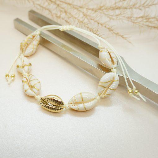 Muschel-Armband mit Kauri-Muscheln gesprenkelt und goldener Kauri-Muschel auf beigen Band.