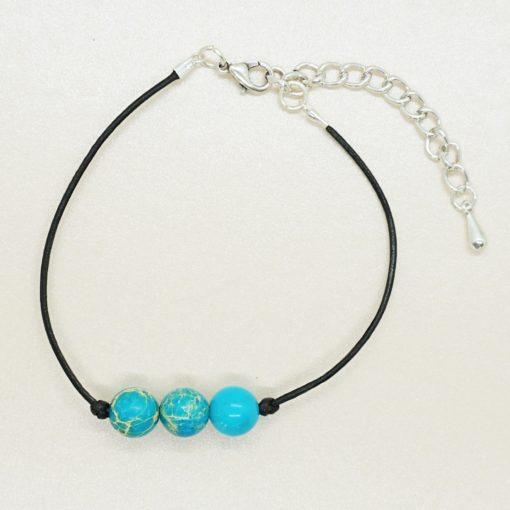 Fußkettchen mit schwarzem Lederband und blauen Perlen.