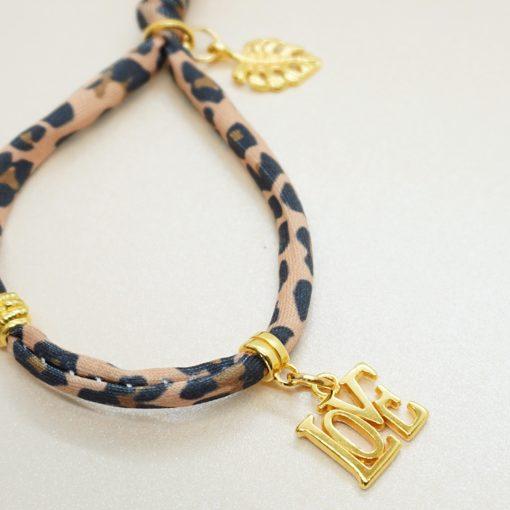 Elastisches Armband mit goldenen Charms in braun.