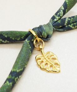 Elastisches Armband mit goldenen Charms in grün.